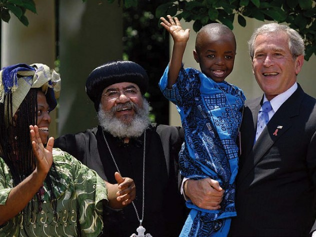 George W. Bush, speaking about PEPFAR (the global AIDS initiative) and holding Baron Mosima Loyiso Tantoh, with Kunene Tantoh, the boy's mother, then suffering from AIDS, and Bishop Paul Yowakim, May 30, 2007, the White House