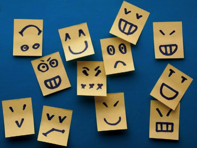 Multiple small paper tabs, each decorated with a simple line drawing of a different facial expression