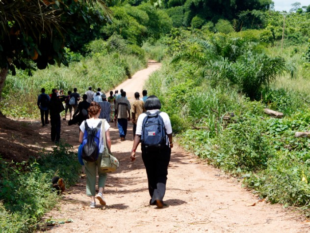 The students and a group of farmers walk along a road to a cacao farm in Bonsaaso district, a part of the UN Millennium Villages Project.