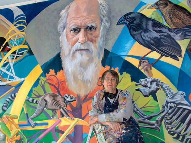 Fichter stands in front of <i>From Orchids to Octopi: The Evolution Mural,</i> which features Charles Darwin.