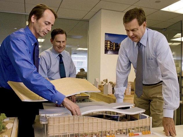 Principals Clifford Gayley, Douglas Johnston, and Rawn discuss a model in their office.