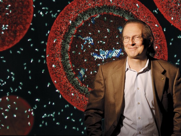 Jack Szostak, professor of chemistry and chemical biology and professor of genetics. Behind him is an illustration of a protocell, a vesicle containing fragments of RNA.