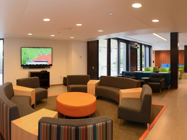 Couches, a flat-screen TV, multicolored chairs, and a brand-new kitchen have transformed the basement of the newly renovated Old Quincy into an appealing community room.