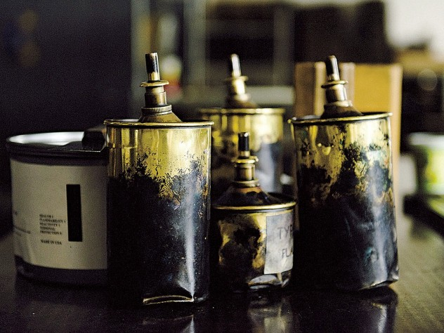 A can of black ink (on the left) and brass cans of type wash