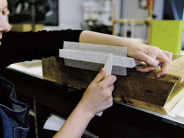 Sarah Songer applies crash (coarsely woven cloth) to strengthen a book's sewn spine