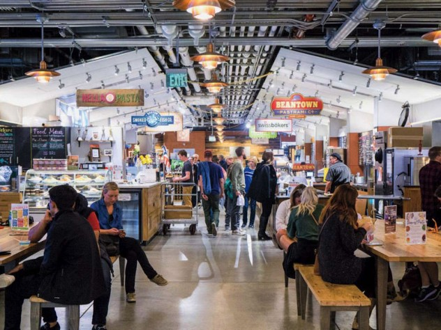 An indoor photo of people eating and shopping at Boston Public Market