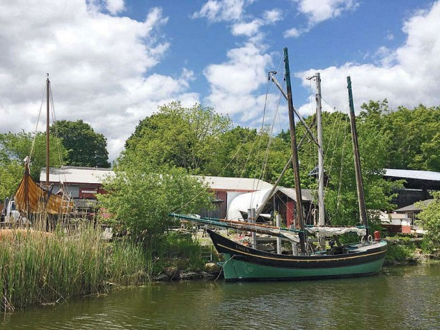 A boat, sails furled, docked near the Essex Historical Society and Shipbuilding Museum.