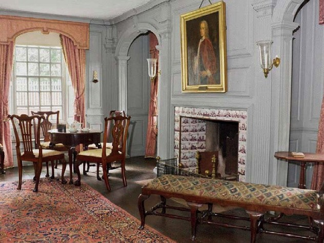 A grand reception room in the main house with an oil portrait hanging above the elegant fireplace.