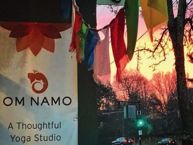 The entrance to Om Namo Yoga Studio, with prayer flags hanging high against a twilight sky.
