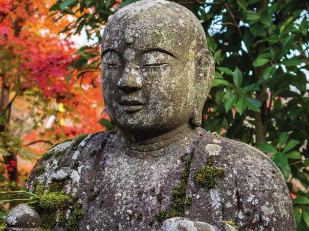 A stone statue of the Buddha appears against a background of colorful autumn leaves.