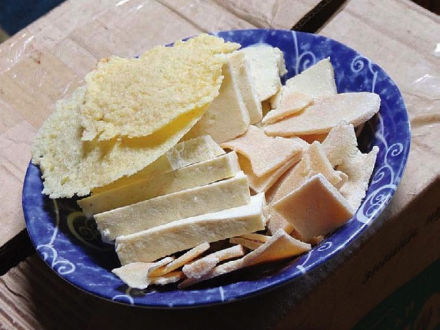 A blue plate displays half a dozen different dairy products that are staple foods of people living on the Eastern Steppe.