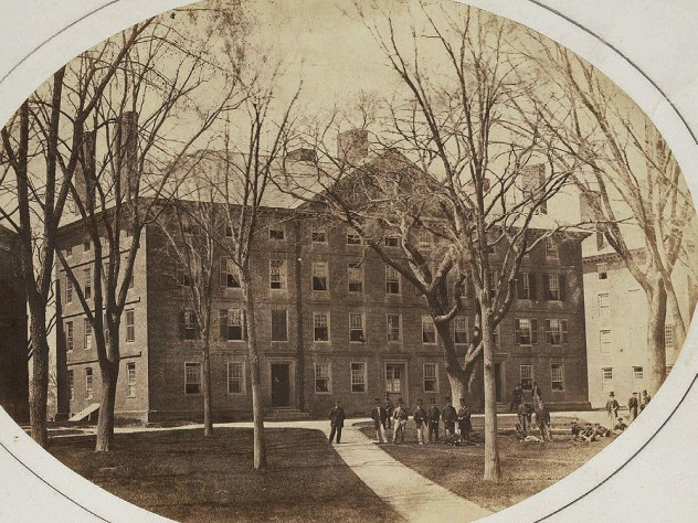"""Old photograph of Hollis Hall with students gathered around the large """"Rebellion Tree"""" in front of the building."""
