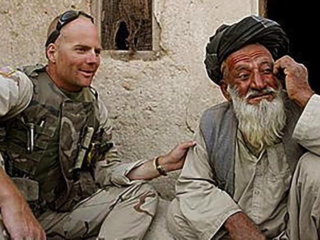 Photograph of Kit Parker on duty in Afghanistan, spring 2003, with a village leader in Kandahar Province