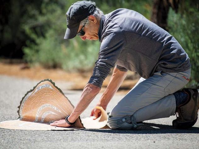 Gilens kneeling on a paved walkway in South Lake Tahoe, installing the artwork