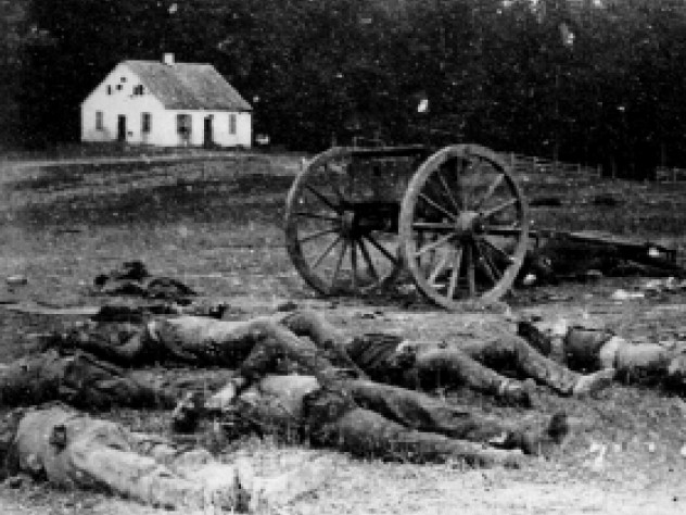 Dead Confederate artillerymen grouped near one of their limbers after Antietam. In the background is a Dunker church, built by a German Baptist pacifist sect.