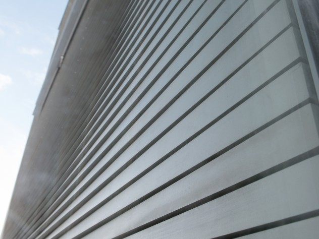 The wood cladding is flat at the corners, shiplap-style, but with gaps between the pieces of wood. Moving away from the corners, the wood has been milled so that it appears to swell outward to resemble clapboard, before retreating again to a purely horizontal plane. Each of the 18,000 pieces of Alaskan yellow cedar, cut by a computer-assisted saw, bears a brass tag with a number that identifies it and its particular shape.