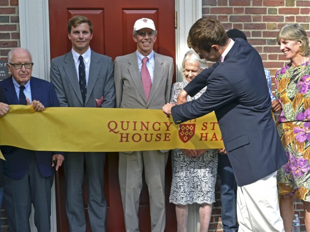 Geyser University Professor emeritus Henry Rosovsky (at left) and members of the Stone family, including grandson Robert Stone '12, Gregg Stone '75, J.D. '79, Marion (Rockefeller) Stone, and Jennifer P. Stone '80, M.D. '86, together with Quincy residents Franco Iudiciani '16 (far left) and Onyeka Nnaemeka '16 (obscured at right), witnessed grandson Eric Green '16 cut the ribbon that officially opened Stone Hall's F entry.