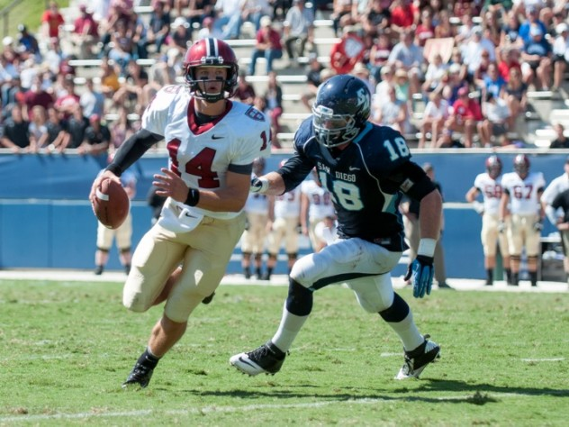 In his debut as Harvard's starting quarterback, junior Conner Hempel (14) threw for 345 yards and four touchdowns. The pursuing San Diego defender is end Blake Oliaro.