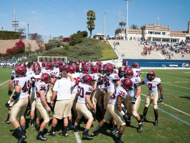 <strong>On the road:</strong> Crimson team members huddled before taking the field at Torero Stadium for Harvard's first West Coast game since 1949. The University of San Diego's small but picturesque facility has a seating capacity of 6,000.