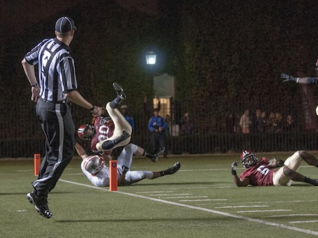 Safety Jaron Wilson (30) hurtled into the end zone after a 51-yard interception return that helped Harvard to a 21-13 lead late in the second period of the Brown game. Cornerback Brian Owusu (6), at right, cleared the way with a devastating block just in front of the goal line.