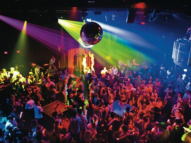 A disco ball and DJ overlook the <i>Donkey Show</i> audience as cast members enact a scene.