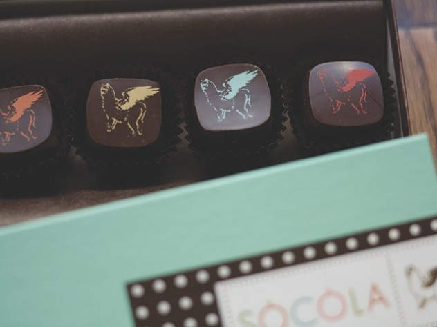 "The whimsical Sôcôla logo, a winged alpaca nicknamed ""Harriet,"" appears in various colors on some of the truffles."