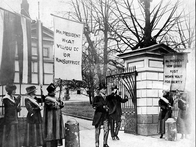 "President Wilson passes ""Silent Sentinels"" as he leaves the White House grounds."