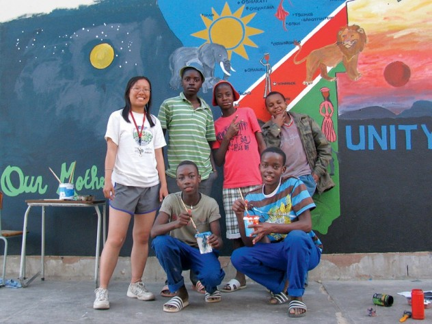 Xue standing in front of the mural that she and her students painted together, an elaborate map of Namibia