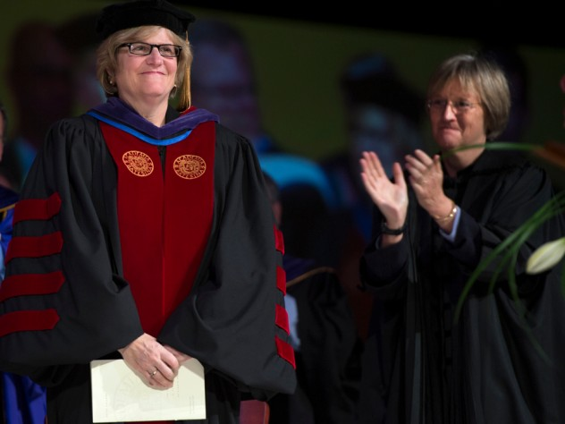 Harvard president Drew Faust, right, stands as Clayton Spencer is introduced as the eighth president of Bates College on October 26, 2012.