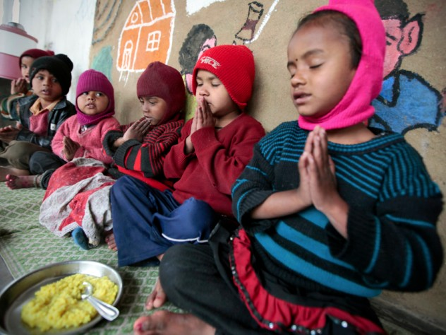 At the crèche, children receive food, education, healthcare, and access to clothing for purchase at low prices. Here, a nondenominational prayer before mealtime. Children on the construction sites come from India's various faiths: Hindu, Muslim, Sikh, and more.