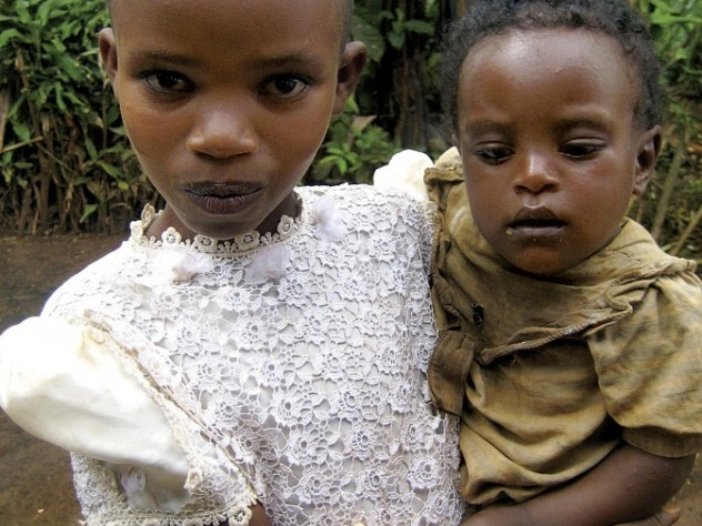 A war-affected girl in Rwanda cares for her younger sibling.