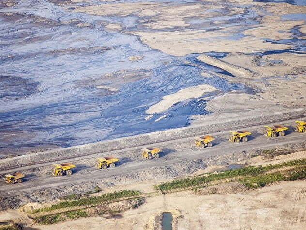 Huge dump trucks lined up in 2012 to transport tar sand from a surface mine, Fort McMurray, Alberta