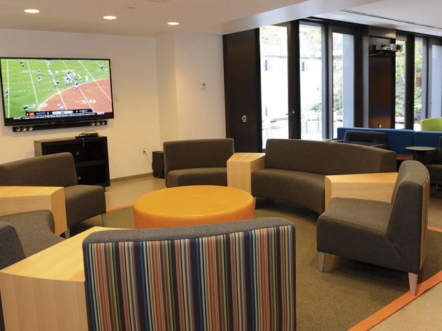 Recent renovations in Old Quincy, now renamed Stone Hall: a new community room with couches, flat-screen TV, a new kitchen, and a below-grade terrace outside the glass doors