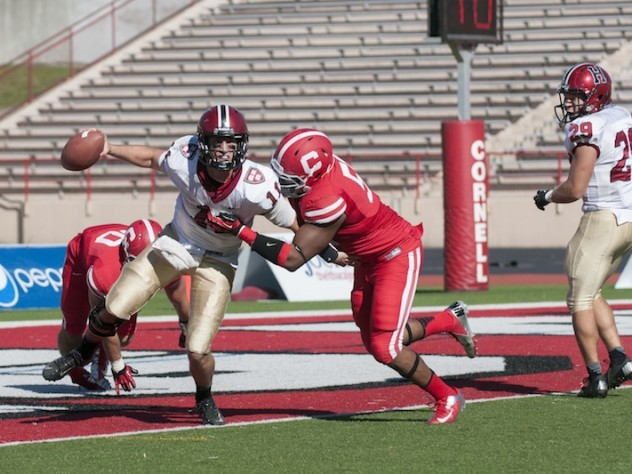 Crimson quarterback Michael Pruneau was almost trapped for a safety by Cornell linebacker Tre' Minor in the final quarter at Schoellkopf Field. Pruneau escaped, and directed a late drive that gave Harvard a 34-24 victory over the Big Red. At right is tailback Paul Stanton Jr., the game's top ground-gainer.