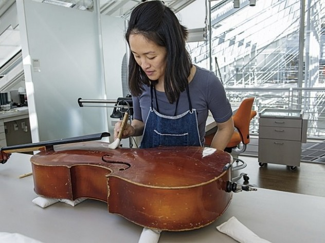 Angela Chang, assistant director and conservator of objects and sculpture, readying a cello for display.