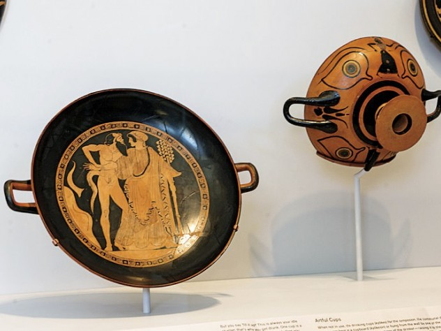 In an installation of Greek vases, drinking bowls are displayed so the decorations can be seen as they would have been when in use—both inside and out—by the drinkers and their companions.