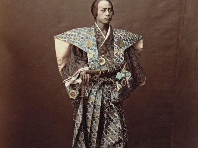 1870s Japan: a hand-tinted albumen print by Raimund von Stillfried showing a man costumed as a samurai warrior