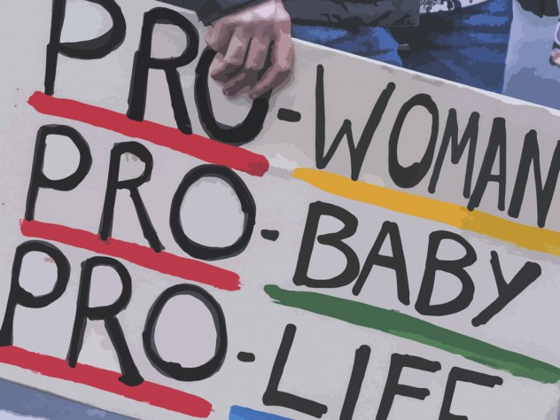 "An activist holding a poster: ""Pro-Woman, Pro-Baby, Pro-Life."""