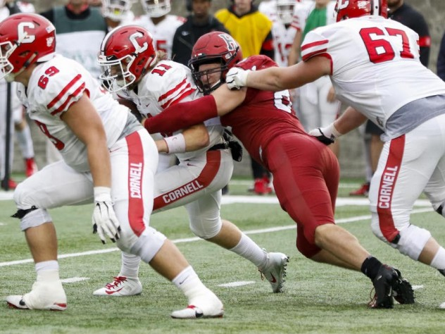 Harvard's Brogan McPartland breaks through to tackle Cornell quarterback Richie Kenney for a loss. In his first 2019 appearance, the senior defensive lineman had two of the Crimson's six sacks.