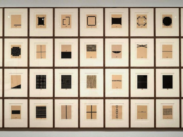 A grid of of 36 abstract black-and-white prints, each representing some aspect of the homes that artist Zarina has lived in, with Urdu and English inscriptions under each