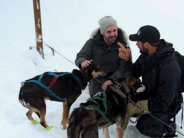 Two men kneeling down to play with sled dogs in the snow