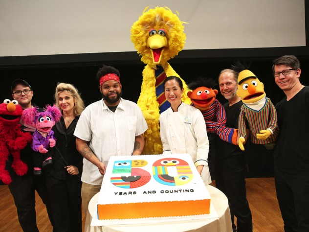 Two bakers present a large birthday cake, surrounded by Muppets and their puppeteers.