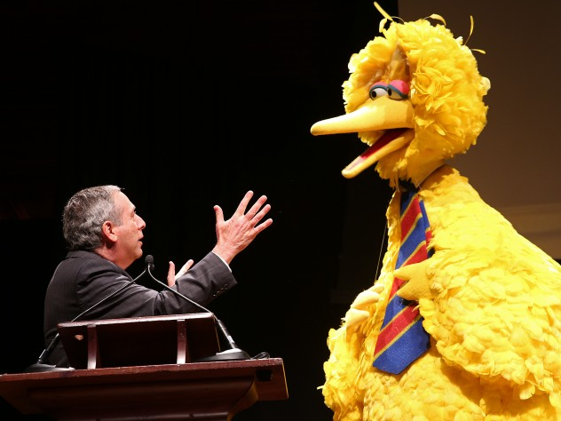 President Bacow and Big Bird talking on stage