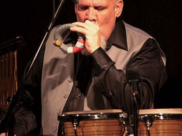 Percussionist Manolo Badrena playing a percussion instrument.