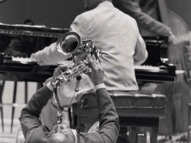 """Jazz artist Walter Blanding playing the saxophone on his back on the floor, """"demonstrating"""" styles of John Coltrane, 2002"""