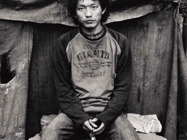 Black-and-white photo of a younger man, wearing jeans and an American hockey T-shirt, sitting on a makeshift stone seat, and holding a set of keys, looks straight at the camera.