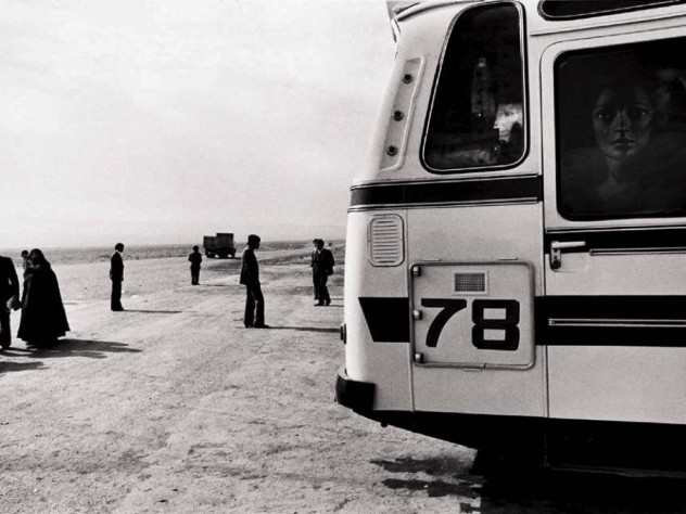 Black-and-white photo of a bus, dominating the right half of the photograph, while a handful of people, and a truck driving toward the horizon, appear as small figures in the left half.