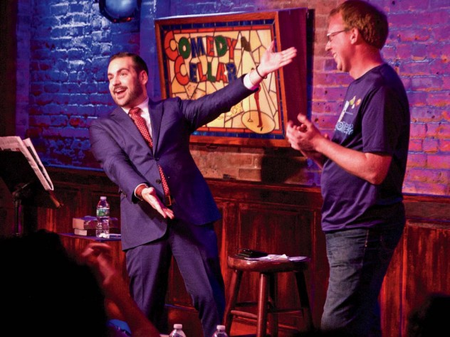 Greenbaum excitedly gesturing toward an audience member on stage at the Comedy Cellar