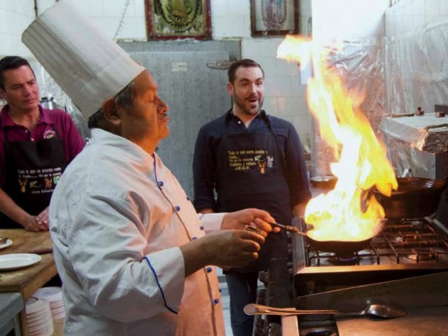Two men look on while a chef cooks a flaming dish over a stove.
