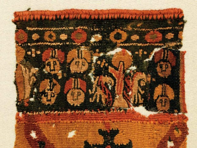 A colorful Byzantine funerary tunic fragment depicts faces and vegetal patterns with a border of gemstones.